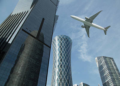 Photograph - Commercial Jet Flying Over Skyscrapers by Buena Vista Images