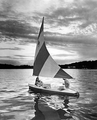 Young Man Photograph - Couple Enjoys A Sunset Sail by Underwood Archives