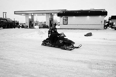 Sask Photograph - couple on a snowmobile leaving a gas station Kamsack Saskatchewan Canada by Joe Fox