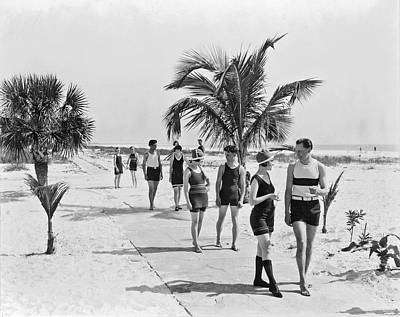 Couples Strolling Along The Pathway On The Beach. Print by -