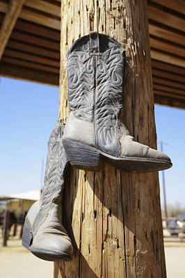 Cowboy Boots Hanging From A Post At A Print by Peter Carroll