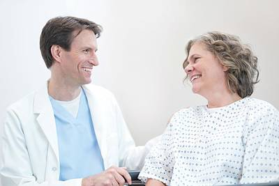 Doctor Smiling At Woman Patient Art Print by Science Photo Library