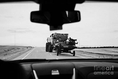 driving behind combine harvester on road in Saskatchewan Canada Art Print by Joe Fox