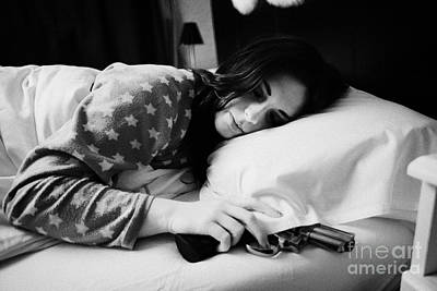 Early Twenties Woman With Hand On Handgun Under Pillow At Night In Bed In A Bedroom Art Print by Joe Fox