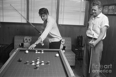 Musicians Photo Rights Managed Images - Elvis Presley and Vernon Playing Bumper Pool 1956 Royalty-Free Image by The Harrington Collection