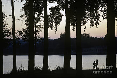 Family Silhouetted By Lake Art Print by Jim Corwin