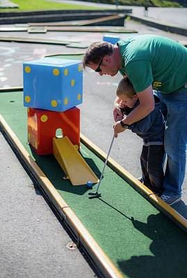 Father Helping Son To Play Mini Golf Art Print