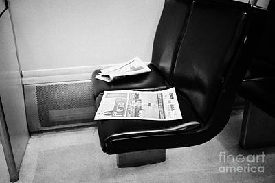 On Paper Photograph - free metro paper discarded on seat on board canada line skytrain Vancouver BC Canada by Joe Fox