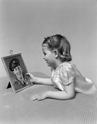 Girl Looking At Picture Of Father Art Print by H. Armstrong Roberts/ClassicStock