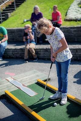 Candid Photograph - Girl Playing Mini Golf by Samuel Ashfield