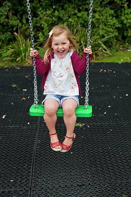 Child Swinging Photograph - Girl Playing On A Swing by Ian Hooton