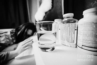 Glass Of Water And Bottles Of Pills On Bedside Table Of Early Twenties Woman In Bed In A Bedroom Art Print by Joe Fox