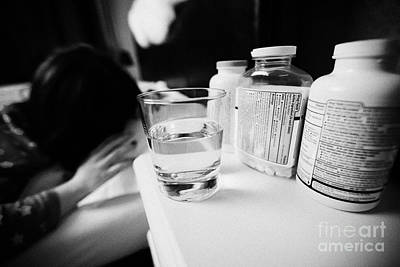 Glass Of Water And Bottles Of Pills On Bedside Table Of Early Twenties Woman Waking In Bed In A Bedr Art Print by Joe Fox