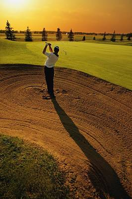 Sports Royalty-Free and Rights-Managed Images - Golfer Taking A Swing From A Golf Bunker by Darren Greenwood