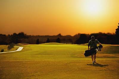 Natural Finish Photograph - Golfer Walking On A Golf Course by Darren Greenwood