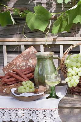 Wooden Ware Photograph - Grapes, Bread, Sausages And Wine On Wooden Bench In Front Of Farmhouse by Eising Studio - Food Photo and Video