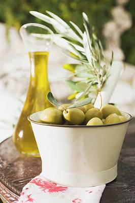 Green Olives, Olive Sprig And Olive Oil On Table Out Of Doors Art Print