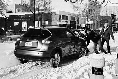 group of men pushing car stuck in deep snow on downtown city street Saskatoon Saskatchewan Canada Art Print by Joe Fox