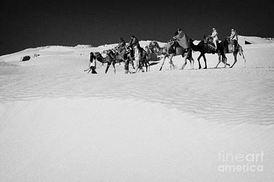 group of tourists in desert dress on camel back being taken through the sand dunes and ruins sahara desert at Douz Tunisia Art Print by Joe Fox