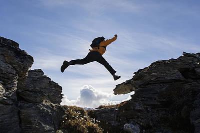 Hiker Leaps Between Rocks Near Noatak Art Print by Scott Dickerson