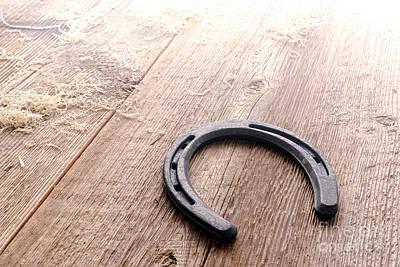 Horseshoe On Wood Floor Art Print by Olivier Le Queinec