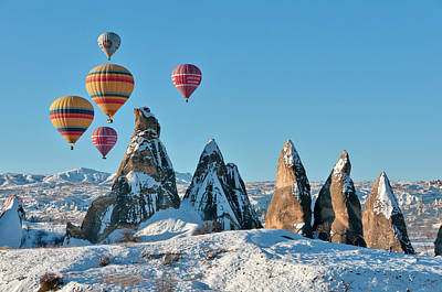 Photograph - Hot Air Balloons Over Snow Covered Rock by Izzet Keribar
