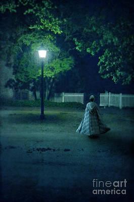 Streetlight Photograph - Lady In Vintage Clothing Walking By Lamplight by Jill Battaglia