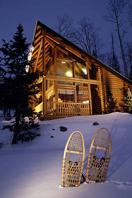 Lighted Cabin With Snowshoes In Front Print by Michael DeYoung