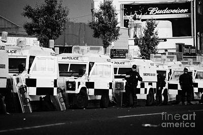 Line Of Psni Landrovers And Officers On Crumlin Road At Ardoyne Shops Belfast 12th July Art Print by Joe Fox