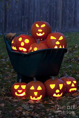 Photograph - Lit Carved Pumpkins In Wheelbarrow by Jim Corwin