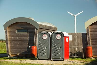 Log Cabins Photograph - Log Cabins And A Wind Turbine by Ashley Cooper