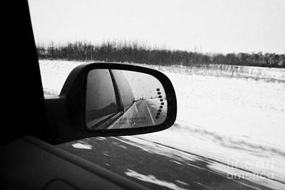 Wing Mirror Photograph - looking at side view mirror winter driving along Saskatchewan highway 11 from Saskatoon to Regina Ca by Joe Fox