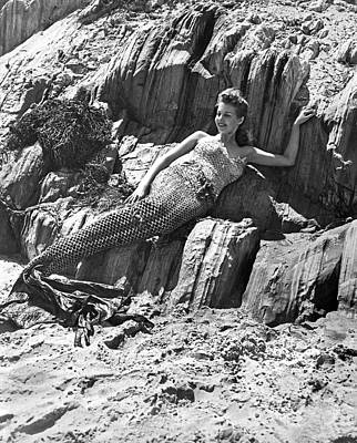 Black Mermaid Photograph - Lounging Mermaid On The Rocks by Underwood Archives
