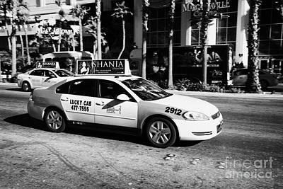Speeding Taxi Photograph - lucky cab speeding down Las Vegas boulevard Nevada USA deliberate motion blur by Joe Fox