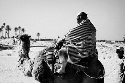 Camel Photograph - male tourist in desert clothing being led on the back of a camel into the sahara desert at Douz Tunisia by Joe Fox