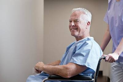 Man In Hospital Gown In Wheelchair Art Print by Science Photo Library