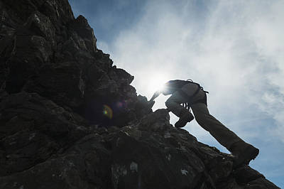Man Scrambling Up Ridge In The Black Art Print by Ian Cumming