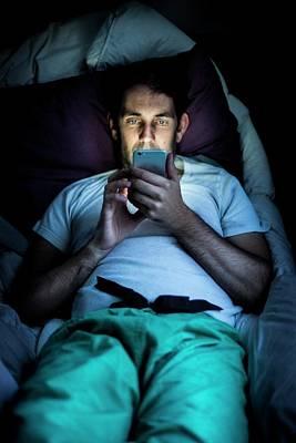 Man Using Smartphone In Bed Art Print by Samuel Ashfield