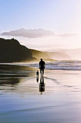 Man Walking The Dog On Beach Art Print by Mikel Martinez de Osaba