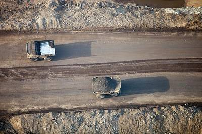 Destruction Photograph - Massive Dump Trucks Loaded With Tar Sand by Ashley Cooper