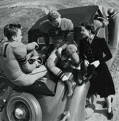 American Car Photograph - Model By Football Players On A Car by Toni Frissell
