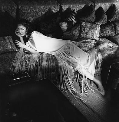 Earrings Photograph - Model Lying On A Couch In A Antonelli Poncho by Henry Clarke