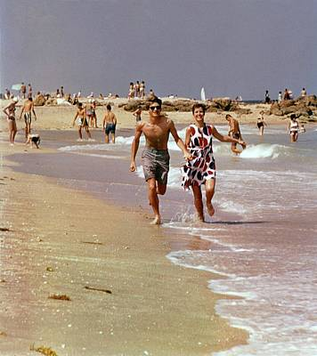 Two People Holding Hands Photograph - Models Running On A Beach by William Connors