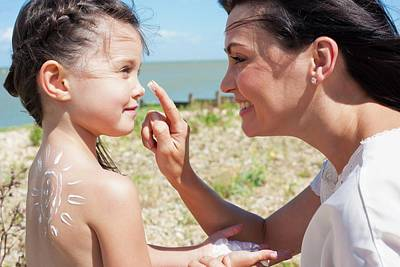 Mother Applying Suncream To Daughter Art Print by Ian Hooton