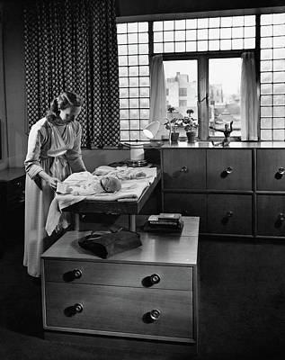 Mrs. Morris Sanders Dressing A Baby On Morris Art Print by Andr? Kert?sz