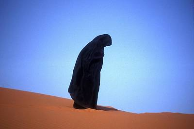 Muslim Woman Praying On A Sand Dune Photo Art Print by .
