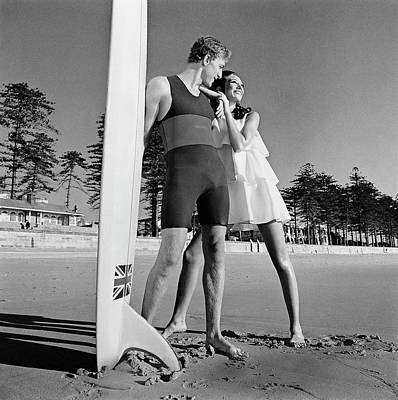 Nat Young And Marisa Berenson By A Surfboard Art Print by Arnaud de Rosnay