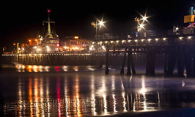 Photograph - Night On Santa Monica Beach Pier With Bright Colorful Lights Reflecting On The Ocean And Sand Fine A by Jerry Cowart