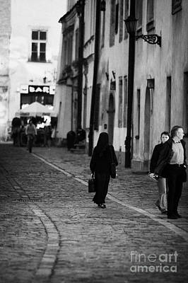 nun with briefcase walking up cobblestone street Kanonicza past tourists in old town krakow Art Print by Joe Fox