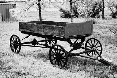 Wooden Farm Wagon Photograph - old wooden and metal farm wagon made from vehicle wheels and axle in depression era leader Saskatche by Joe Fox